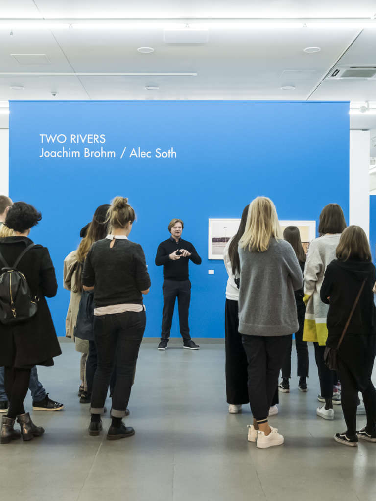 Several persons are listening to man guiding through the exhibtion two rivers