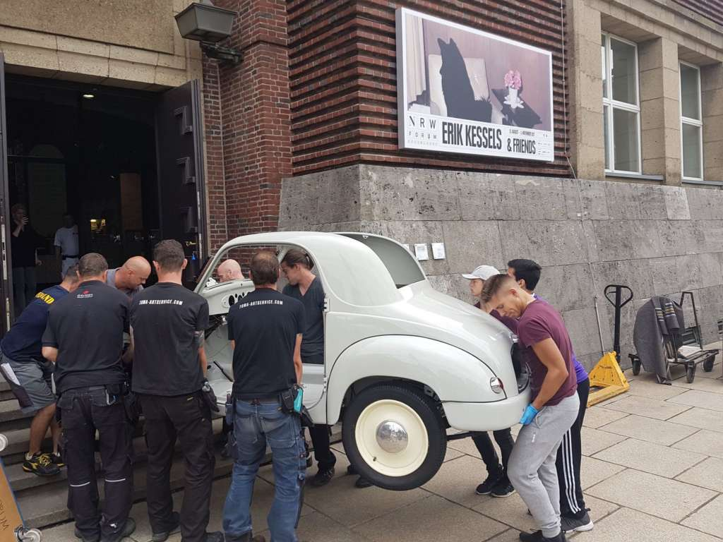 Several craftsmen carrying a oldtimer car into the NRW Forum