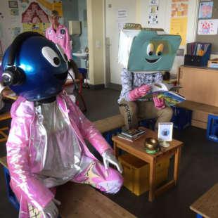 Die Maskottchen des NRW Forums Data und Zip sitzen in einem Klassenzimmer auf Holzbänken und schauen in ein Buch