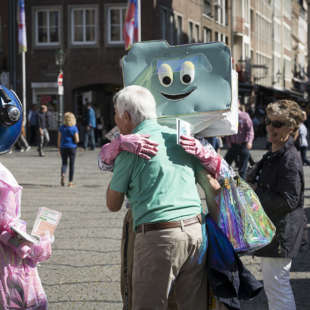 The mascots of the NRW Forum Data und Zip hug an elderly man in downtown Düsseldorf