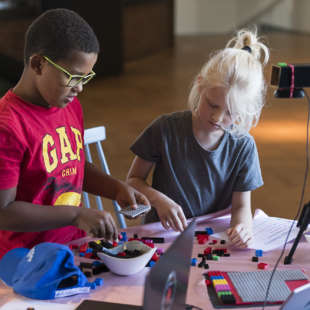 Two children sit at a table and build something from building blocks. On the table is a tripod with a camera and two laptops