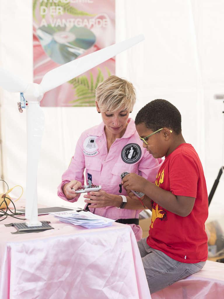 Eine Workshopleiterin erklärt einem Jungen, an einem Tisch sitzend, mit einem Windrad darauf stehend, technische Gerätschaften
