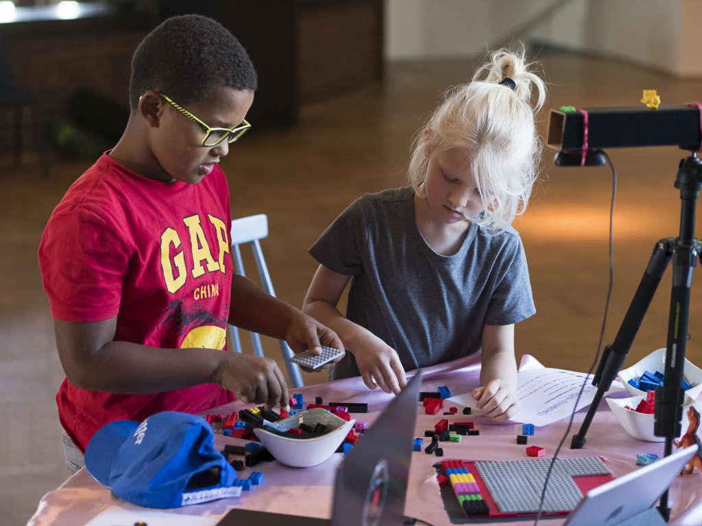 Zwei Kinder sitzen an einem Tisch und bauen aus Bausteinen etwas zusammen. Auf dem Tisch steht ein Stativ mit Kamera und zwei Laptops