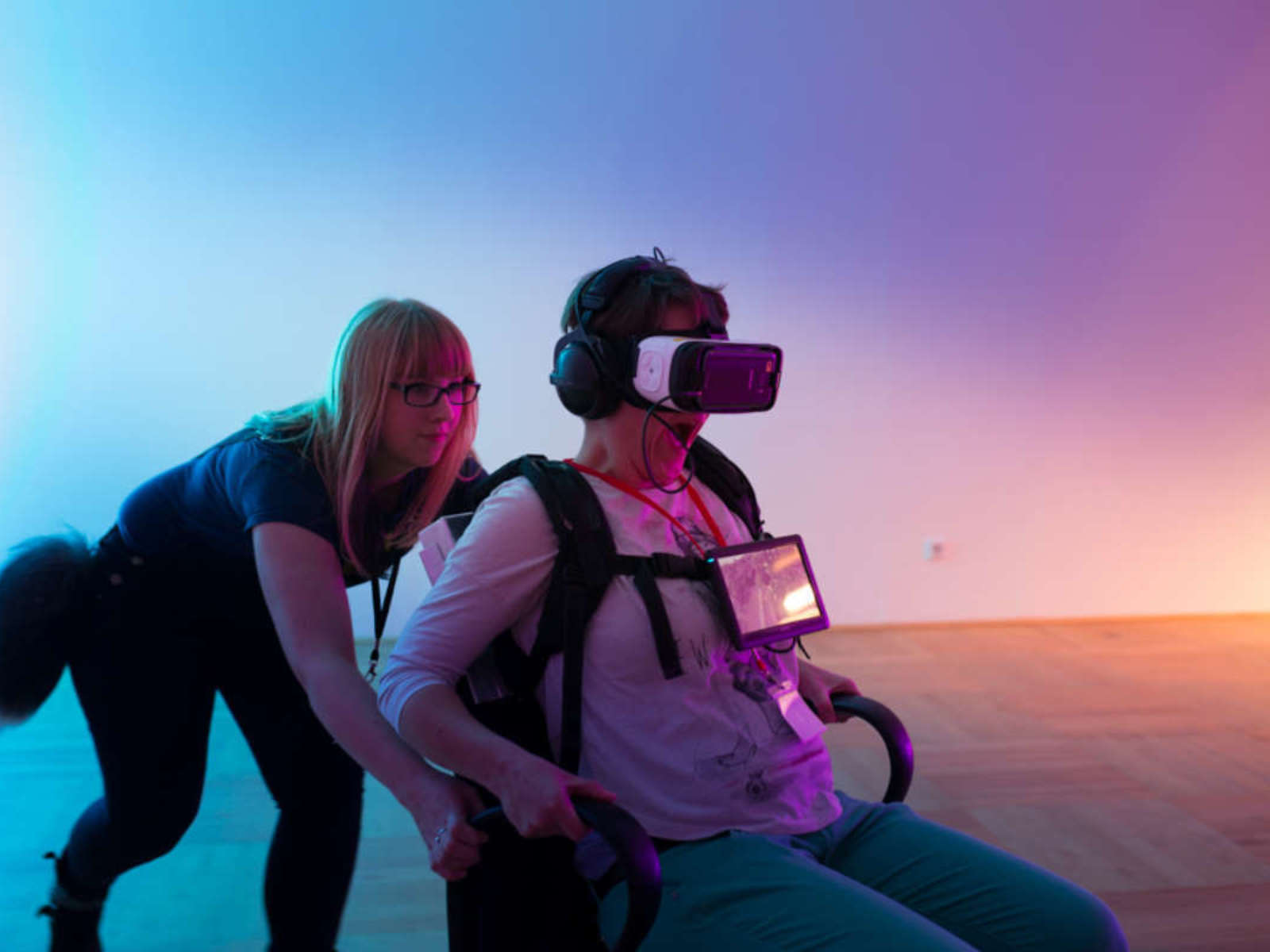 A person with VR glasses on her head sits on an office chair to which he tries to hold on to and is pushed by a young woman