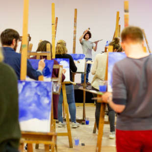 Several people stand with a canvas in front of them in a room and follow the instructions of a teacher while painting