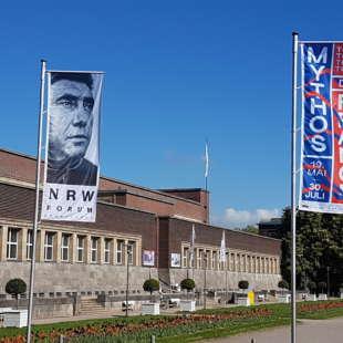 Das Gebäude des NRW Forums von außen betrachtet, mit zwei Flaggen zur Ausstellung Mythos Tour de France davor