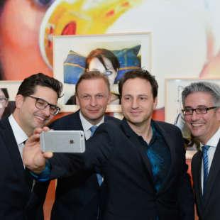 Alain Bieber, künstlerischer Leiter des NRW Forums, macht ein Selfie zusammen mit drei weiteren Personen in Anzügen vor Fotos in einer Ausstellung