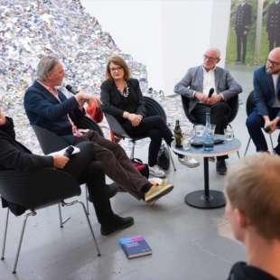 Fünf Personen diskutieren bei einer Podiumsdiskussion vor Zuschauern mit einem Kunstwerk aus Bergen von Fotografien im Hintergrund