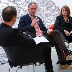 Drei Personen diskutieren bei einer Podiumsdiskussion vor einem Kunstwerk aus Bergen von Fotografien
