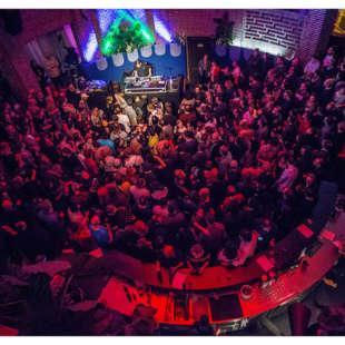 Konzert mit vielen, dicht gedrängten Personen im Publikum sowie ein Musiker auf der Bühne in der Rotunde des NRW Forums