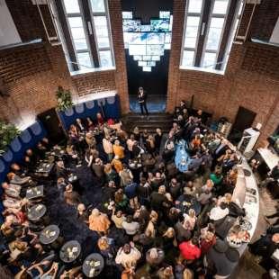 Konzert im NRW Forum mit einem Melodica spielenden Musiker auf einer Bühne mit verschiedenen elektronischen Instrumenten vor tanzendem Publikum