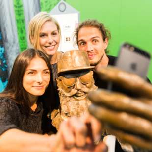 Three people take a selfie with a bust of the musician MC Fitti