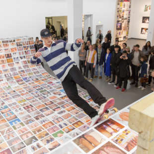 Exhibition view of the exhibition Ego Update with a skateramp covered with photos on which a skater rides while people are watching him