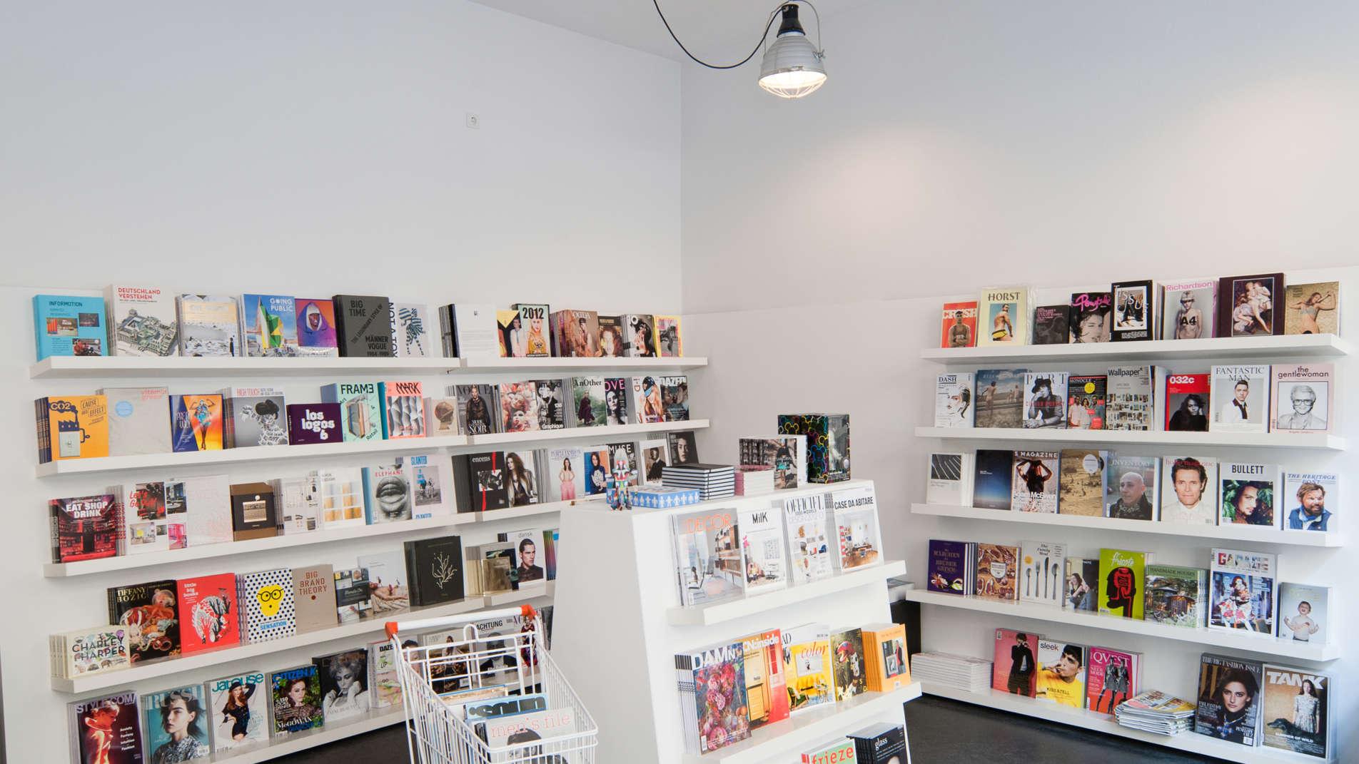 Mehrere weiße Regale mit vielen verschiedenen Büchern und Magazinen