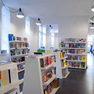 Mehrere weiße Regale mit vielen verschiedenen Büchern und Magazinen in weiß gestrichenem Raum und hell leuchtenden Industrielampen an der Decke