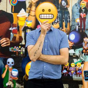 Alain Bieber, künstlerischer Leiter des NRW Forums, hält sich ein auf Pappe gedrucktes Emoji, dass seine Zähne zeigt, vor sein Gesicht