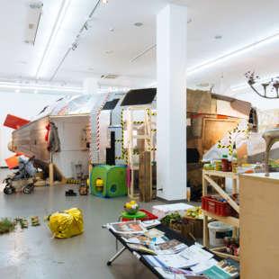 Ausstellungsansicht der Ausstellung Planet B mit einem aus Holz gebauten Raumschiff im Hintergrund und verschieden Möbeln und Pflanzen im Vordergrund