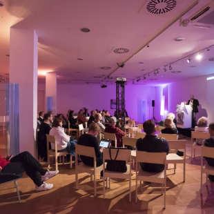 Vortrag mit mehreren Personen im Publikum, die auf Stühlen sitzen und einem Mann, der eine Präsentation vorführt