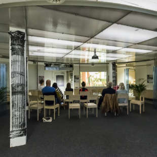 Mehrere Personen sitzen in einem runden, dekorierten Raum auf Stühlen und schauen einen Film, der an eine Wand projeziert wird