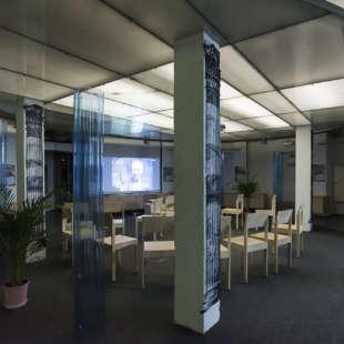 Runder, dekorierter Raum mit Stuhlkreis in der Mitte und einer Präsentation, die an eine Wand projeziert wird