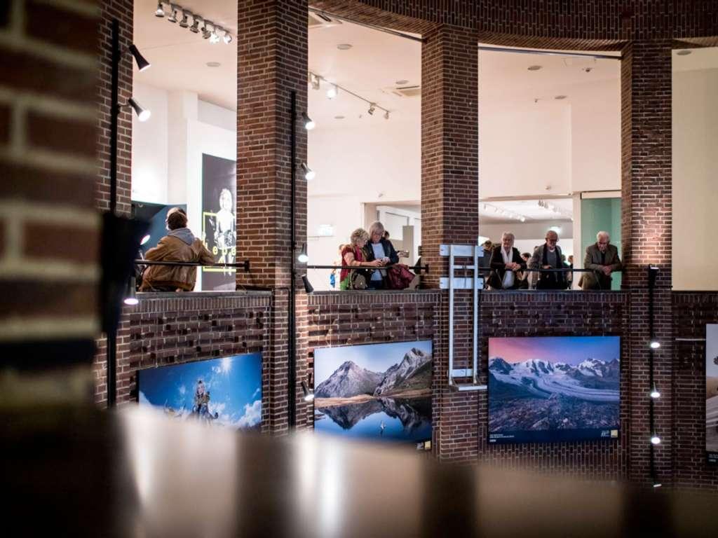 Mehrere Personen stehen im Obergeschoss des NRW Forums an der Galerie und schauen runter in das Erdgeschoss. An der Galerie sind Bilder angebracht