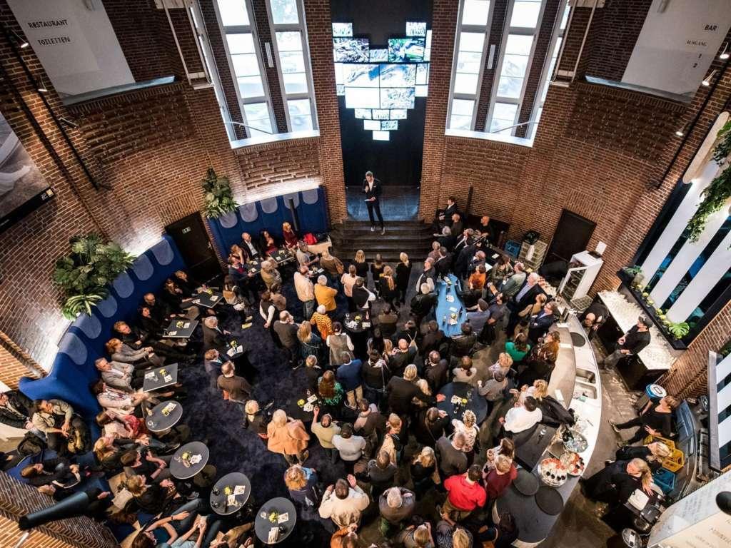 Viele Personen stehen in der Gastronomie Pong des NRW Forums und hören einer Rede zu