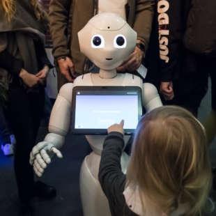 Kind bedient bei einer Veranstaltung mit vielen Leuten im Hintergrund einen weißen Roboter mit Touchscreen