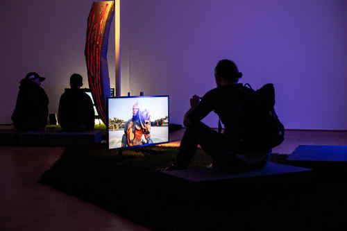 Three people sit in a dark room in front of brightly lit monitors