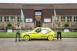 A yellow car in which a man is sitting stands in front of the NRW Forum. On the car it says: Talk to me. I will drive you